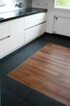 Kontrastreiche Verlegung von Parkett und Fliesen unterstreichen das moderne Erscheinungsbild der Küche